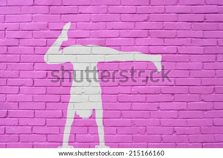 wall of bricks with woman contortionist practicing gymnastic yoga position - stock photo
