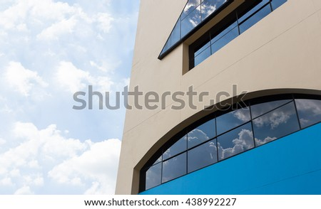 Wall of cream yellow and blue building with big dark clear window reflecting cloudy sky