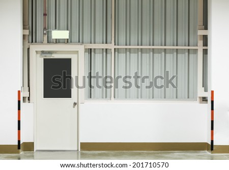 Wall of factory with steel door, nighttime. - stock photo