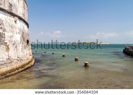 Wall of Fuerte de San Fernando fortress on Tierrabomba island near Cartagna, Colombia. Bateria de San Jose fort in the background. - stock photo