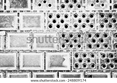 Wall of glass tiles in which some are missing - stock photo
