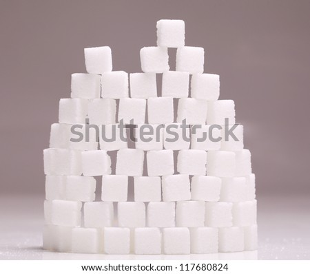 Wall of many white sugar cubes stacked up on grey background