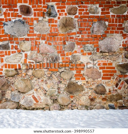 Wall of mixed materials - stone and bricks and a ground covered with snow