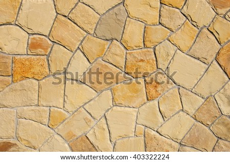 wall of natural stone in various shades of light brown sandstone/sandstone texture background/pattern formed by sandstone rocks of various shapes and colors - stock photo