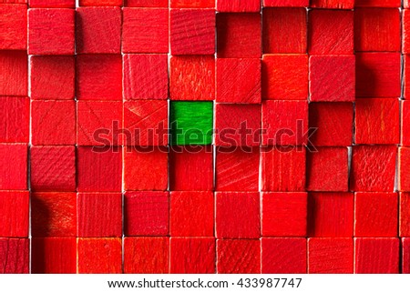 wall of red toy blocks, green block in the middle, concept think different, be unique