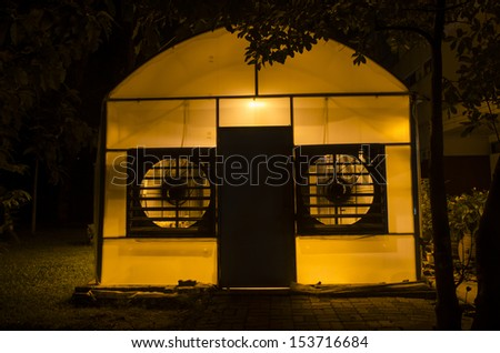 wall of research greenhouse with a large fan open and running, lights inside on at dusk - stock photo