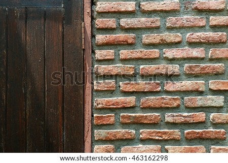 Wall of the house consists of bricks and cement, part of the wooden door