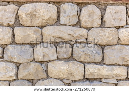 Wall of the house lined with stones - stock photo