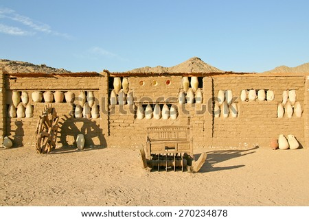 Wall of the old clay house decorated with pots in Africa - stock photo