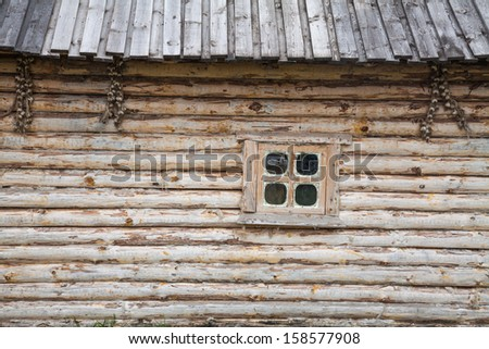 Wall of the old wooden house and a window - stock photo