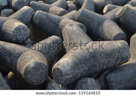 Wall of wave breakers made from cement lying under sunlight at the seashore