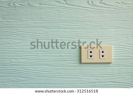 Wall outlets on the pale green wall with wood texture. - stock photo