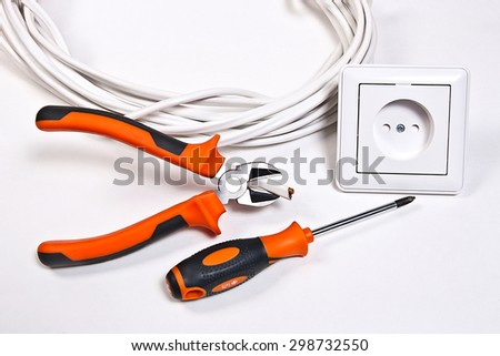 Wall socket, power cable and electrician tools on white background - stock photo
