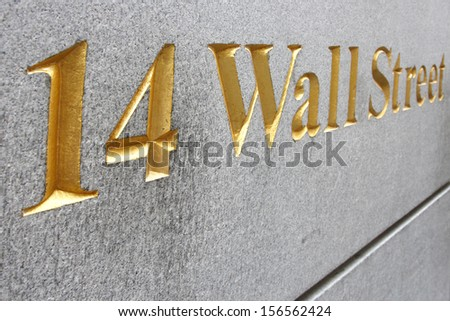 Wall street address  in golden letters embedded  on rough granite wall - stock photo