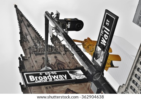 Wall Street and Broadway street signs and traffic light against a Trinity Church. New York City, USA. - stock photo