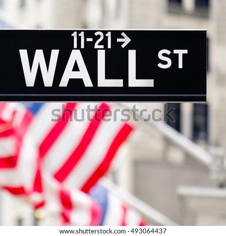 Wall street sign in New York City with out of focus buildings and american flags on the background