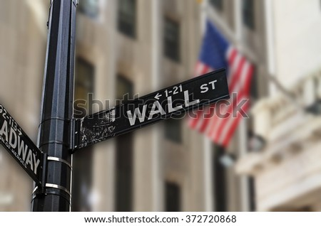 Wall Street sign with American flag and architectural building on the background. - stock photo
