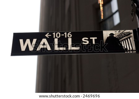 Wall Street street sign against sky and buildings - stock photo
