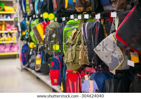 Wall with bags and backpacks in different types and colors in store - stock photo