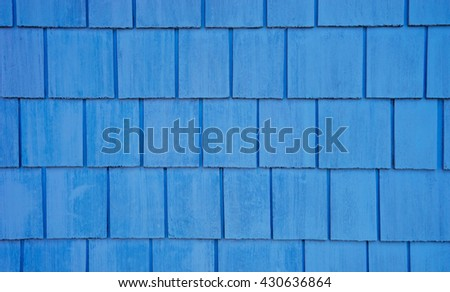 Wall with shingles and weathered blue paint. - stock photo