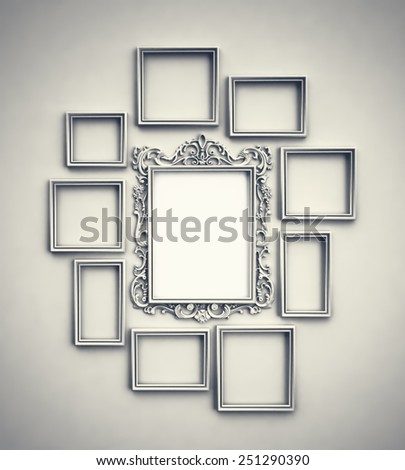 Wall with simple frames surrounding ornamented frame in the middle - stock photo