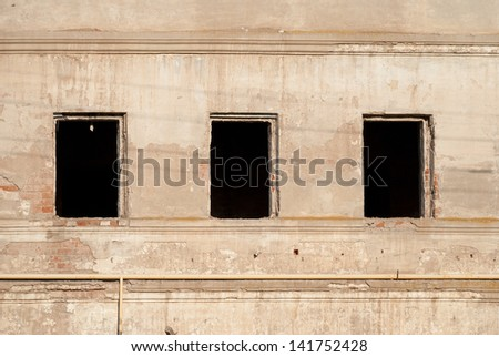Wall with three empty windows without frames - stock photo