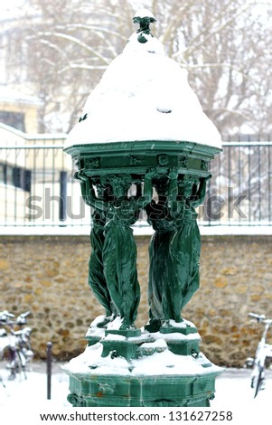 "Wallace fountain in Paris by winter / One of the drinking fountains in Paris so called ""Wallace fountains"" in winter covered by snow. Those fountains are recognized as one of the symbols of Paris - stock photo"