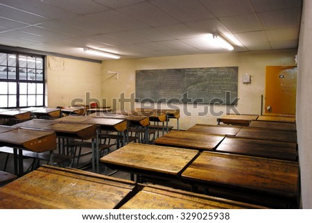 WALLACEDENE, SOUTH AFRICA - AUGUST 3, 2008: The interior of a classroom in a South African township. The blackboard has the current material for the class. The wooden desks are covered with graffiti.