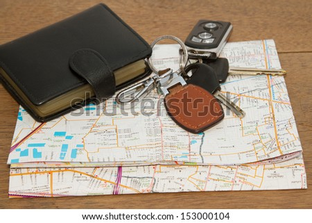 Wallet and car keys on the road map, concept traveling on vacation - stock photo