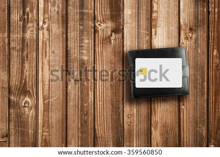 Wallet and credit card on wooden table - stock photo