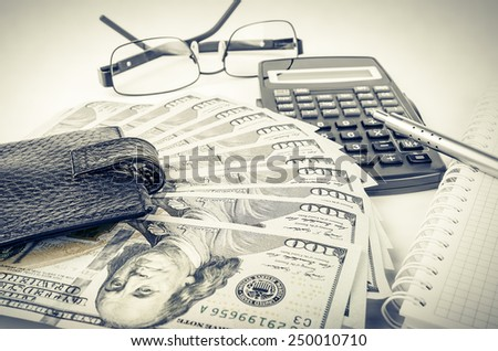 Wallet  calculator glasses and dollars. Blurred background
