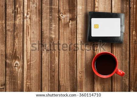 Wallet, credit card and coffee cup on wooden table - stock photo