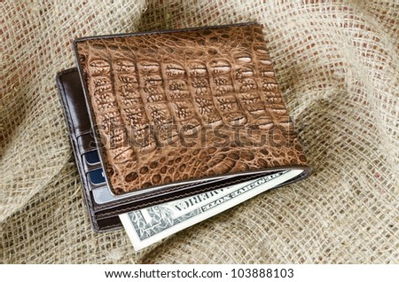 Wallet made of genuine crocodile leather over the linen background