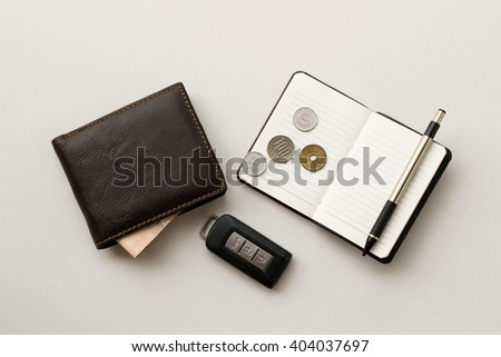 Wallet, notebook with pencil, car key and Yen coin on the white table; Warm tone; Flat lay