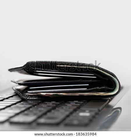 Wallet on laptop keyboard - 1 to 1 ratio - stock photo