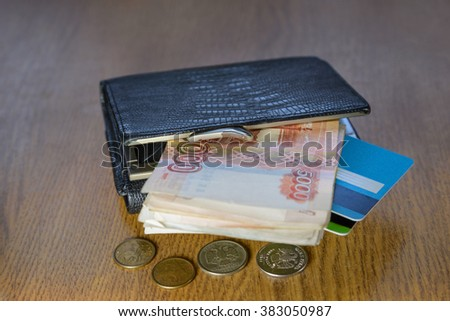 Wallet with credit cards and cash lying on a wooden table