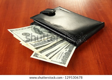 Wallet with hundred dollar banknotes, on wooden background - stock photo