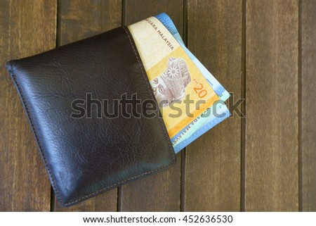 Wallet with Malaysian Ringgit money on classic wood background. - stock photo