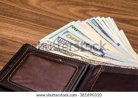 Wallet with us dollar bills on wooden table