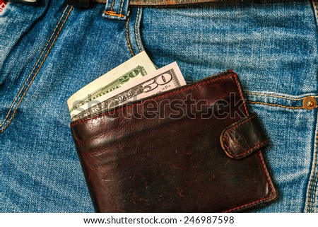 Wallet with US dollars and jeans pocket close-up - stock photo