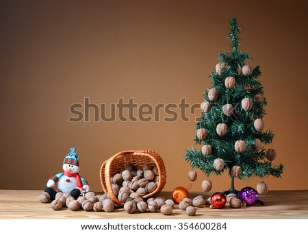 Wallnuts in a wicker basket with a pine tree on a table - stock photo