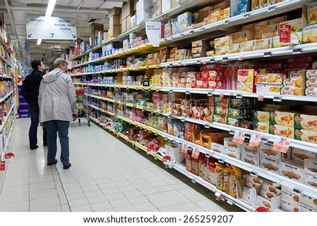 WALLONIA, BELGIUM - OCTOBER 17: Consumers shopping in the Cookies section. Aisle with a variety of packaged biscuits products in a Carrefour Hypermarket on October 17, 2014 in Wavre, Belgium