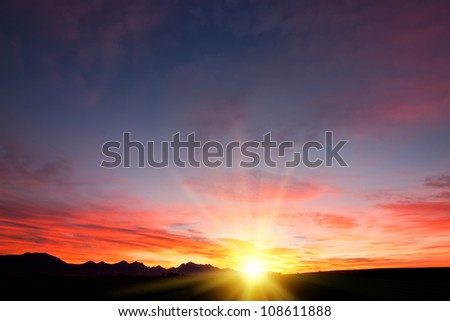 wallpaper background of sun filtered cloudscape morning sunrise over silhouetted mountains - stock photo