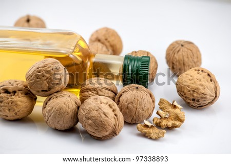 Walnut and a bottle nut oil on the white background