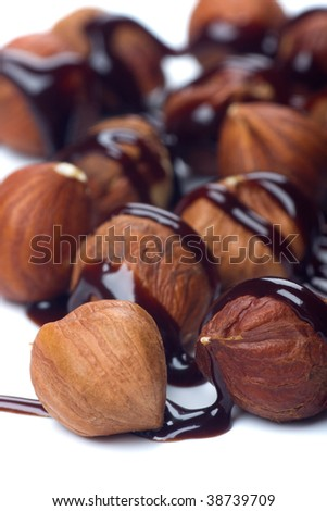 Walnut cores with chocolate topping on white background