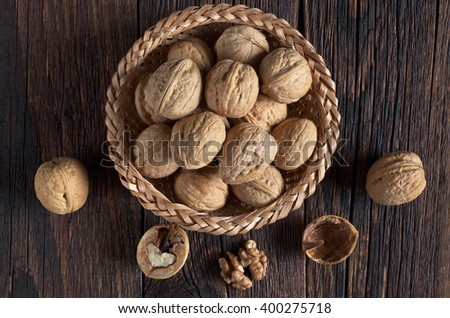 Walnut in bowl and walnuts kernels on dark wooden table, top view - stock photo