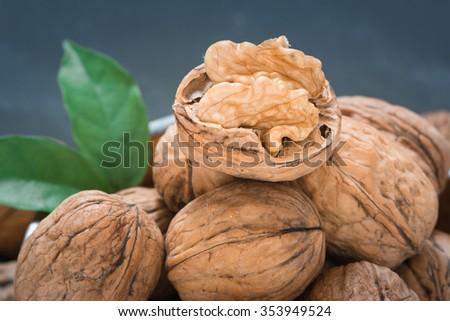 Walnut kernels and whole walnuts on black background - stock photo