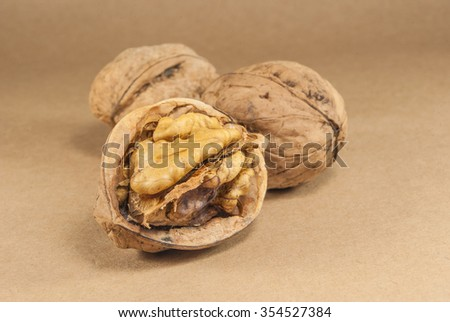 Walnut kernels and whole walnuts on kraft paperf, close up - stock photo