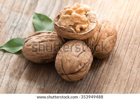 Walnut kernels and whole walnuts on old wood table  - stock photo