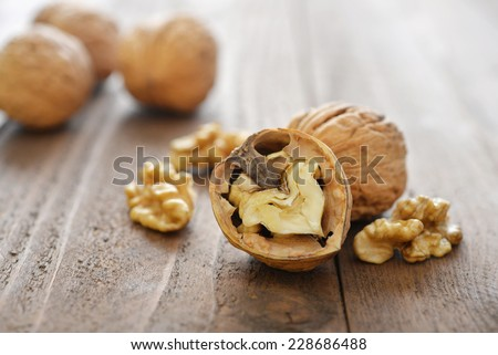 Walnut kernels and whole walnuts on rustic old wooden background - stock photo